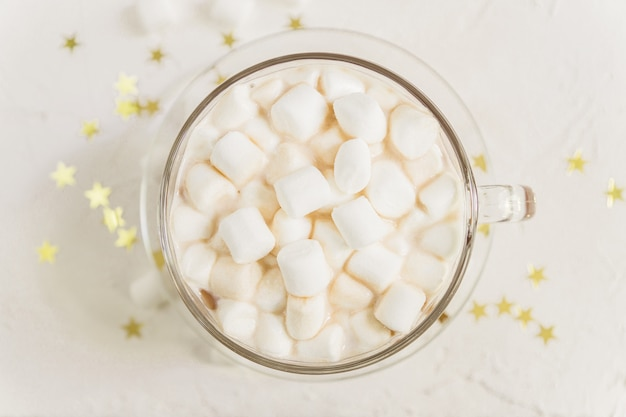 Top view of cup of hot delicious cocoa drink with marshmallows on gold stars Premium Photo
