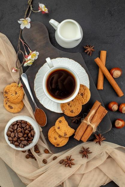 コーヒースターのトップビューカップは、暗い表面のボウルミルクボウルの木製ボードコーヒー豆のクッキースプーンをアニスします 無料写真