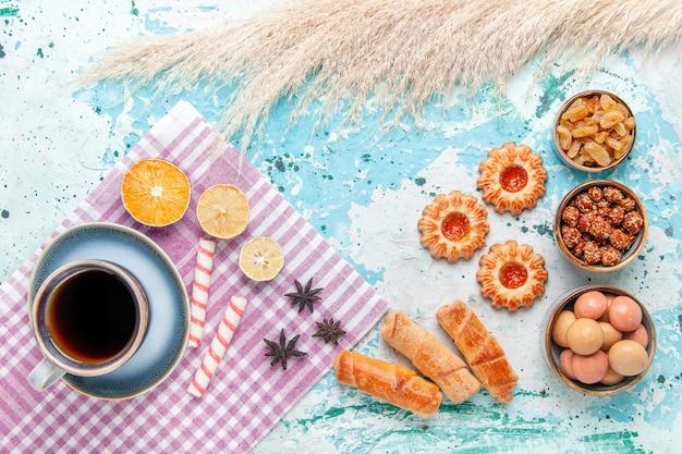 水色の背景のケーキにベーグルとクッキーとコーヒーのトップビューカップは甘い砂糖パイビスケットを焼く 無料写真