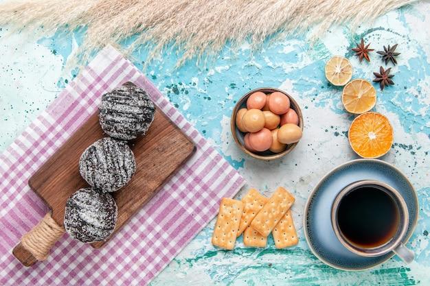 チョコレートのアイシングケーキと水色のデスクケーキにクラッカーとコーヒーのトップビューカップは甘い砂糖パイビスケットを焼く 無料写真