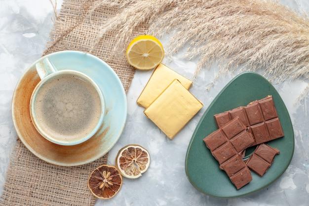Вид сверху чашка кофе с молоком внутри чашки вместе с шоколадом на светлом столе пить кофе молочный стол эспрессо американо Бесплатные Фотографии