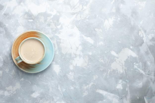 白い机の上のカップの中に牛乳とコーヒーのトップビューカップコーヒー牛乳デスクの色を飲む 無料写真