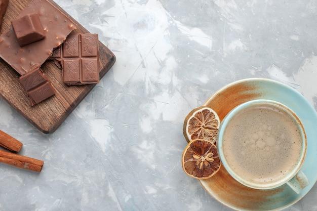 Вид сверху чашка кофе с молоком внутри чашки с шоколадными батончиками и корицей на белом столе пить кофе молочный стол эспрессо американо Бесплатные Фотографии