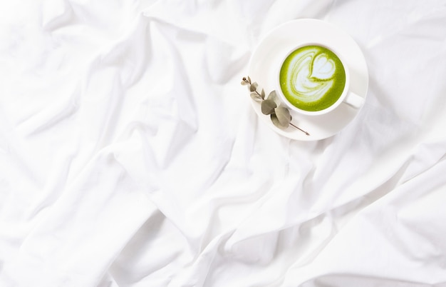 ベッドの中で抹茶ラテのトップビューカップ。居心地の良いフラットレイ。毎朝の日課。コピースペース。コンセプトミニマリズム Premium写真