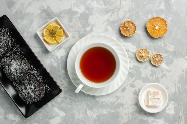 ライトホワイトの机の上にチョコレートケーキとお茶のホットドリンクのトップビューカップ 無料写真