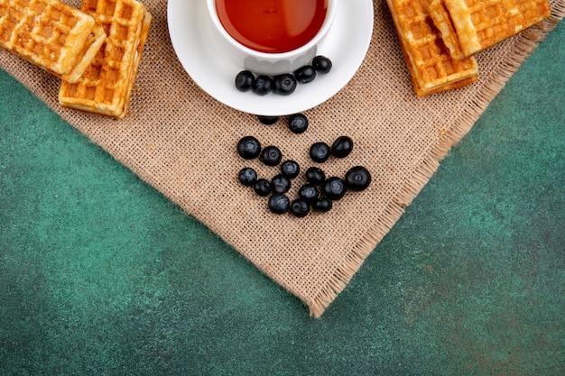緑の背景にブルーベリーとワッフルとお茶のトップビューカップ 無料写真