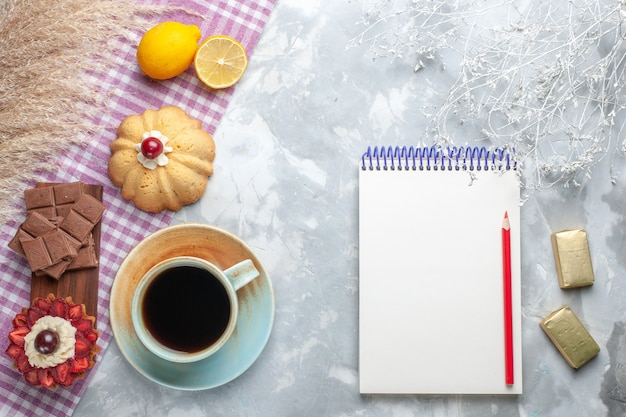白い机の上のケーキレモンメモ帳とチョコレートバーとお茶のトップビューカップケーキスイートシュガーチョコレート 無料写真