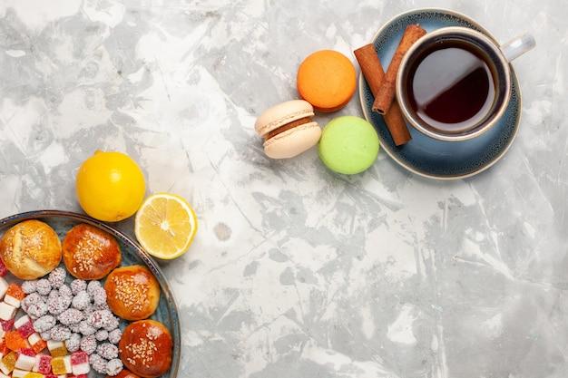 白い表面にキャンディーと小さなケーキマカロンとお茶のトップビューカップ 無料写真