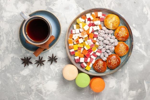 白い表面にキャンディーマカロンと小さなケーキとお茶のトップビューカップ 無料写真