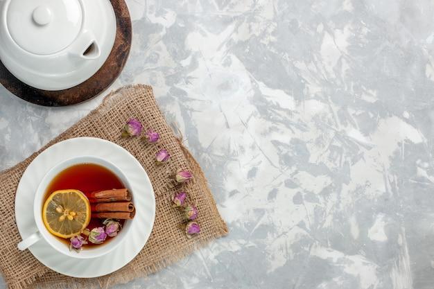 밝은 흰색 표면에 계피와 레몬 차의 상위 뷰 컵 무료 사진