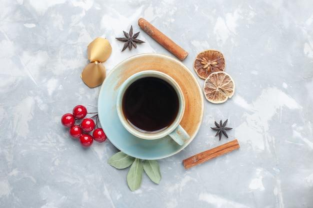 白い机の上にシナモンとお茶のトップビューカップティーキャンディーカラードリンクホット 無料写真