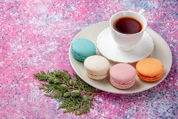 ピンクの表面にカラフルなフレンチマカロンとお茶のトップビューカップ 無料写真