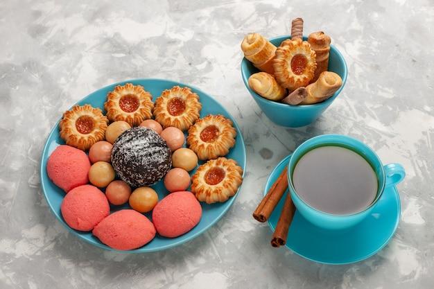 白い表面にクッキーとケーキとお茶のトップビューカップ 無料写真