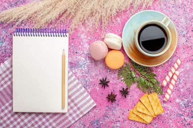 ピンクの表面にクラッカーメモ帳とマカロンとお茶のトップビューカップ 無料写真