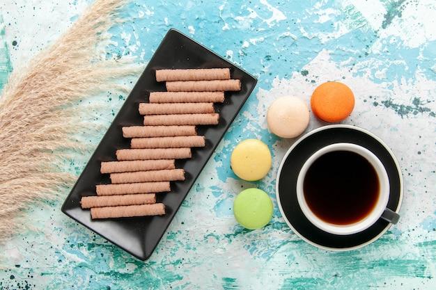 青い表面にフランスのマカロンとクッキーとお茶のトップビューカップ 無料写真