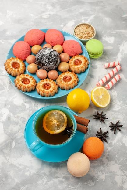白い表面にフランスのマカロンの小さなクッキーとケーキとお茶のトップビューカップ 無料写真