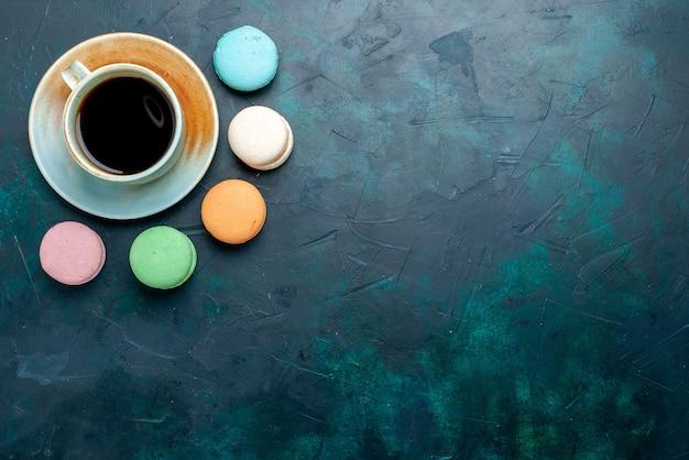Вид сверху чашка чая с французскими макаронами на темно-синем фоне, выпечка, пирог, сахар, сладкий чай Бесплатные Фотографии
