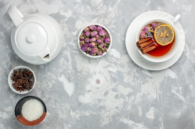 Вид сверху чашка чая с чайником и цветами на белой поверхности Бесплатные Фотографии