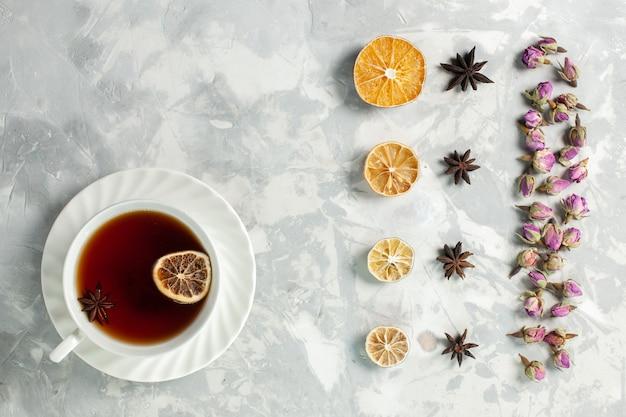 Вид сверху чашка чая с лимоном и цветами на светло-белом столе Бесплатные Фотографии