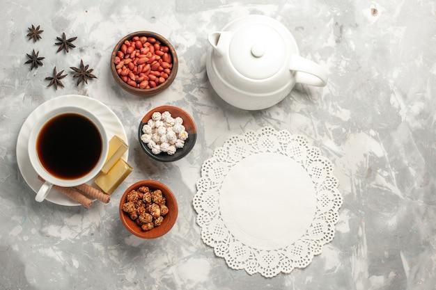 Вид сверху чашка чая с орехами и печеньем на белой поверхности Бесплатные Фотографии