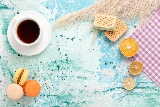 青い背景のクッキービスケットシュガー甘いケーキパイにワッフルとフレンチマカロンとお茶のトップビューカップ 無料写真