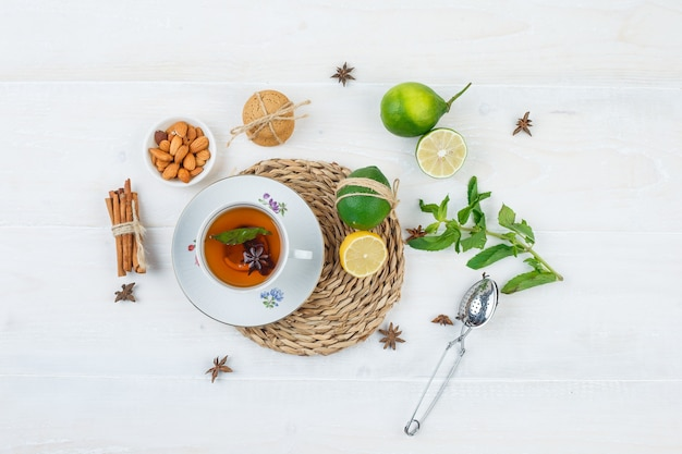 Vista dall'alto una tazza di tè, agrumi e foglie di menta sulla tovaglietta rotonda con lime Foto Gratuite