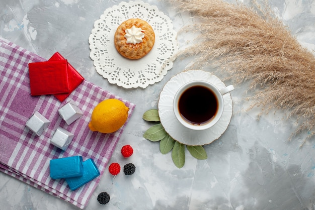 Vista dall'alto della tazza di tè caldo all'interno della tazza bianca con cioccolatini al limone sulla luce, torta di caramelle al cioccolato del tè Foto Gratuite