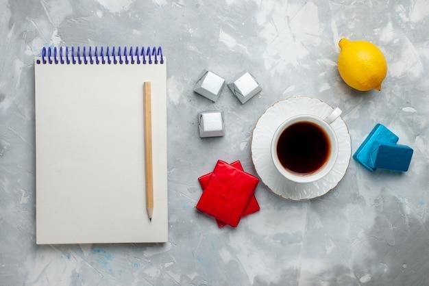Vista superiore della tazza di tè caldo all'interno della tazza bianca con il blocco note delle caramelle di cioccolato del pacchetto anded d'argento sulla scrivania leggera, bevi l'ora del tè del biscotto dolce Foto Gratuite