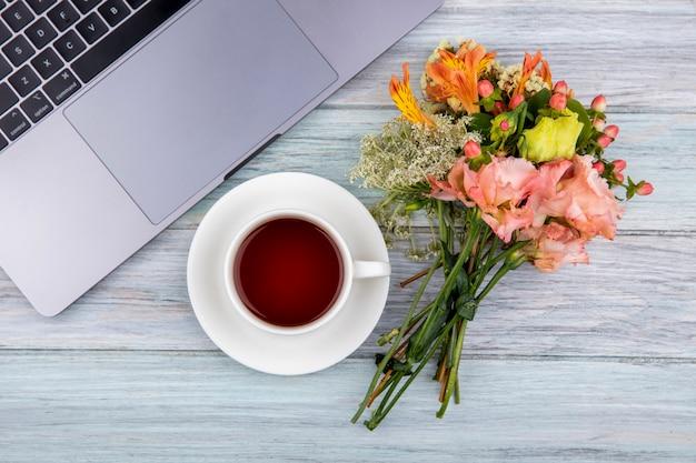 Vista dall'alto di una tazza di tè con bouquet di fiori meravigliosi su legno grigio Foto Gratuite