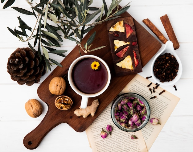 Top view of a cup of tea with chocolate bar with dried fruits and whole walnuts on wood cutting board, dry rose buds in a glass jar and clove spice on white Free Photo