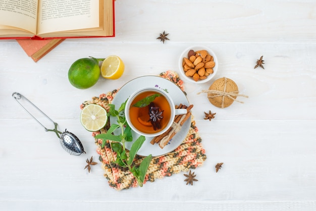 Vista dall'alto della tazza di tè con cannella e limone sulla tovaglietta quadrata con lime, una ciotola di mandorle, colino da tè e libri sulla superficie bianca Foto Gratuite