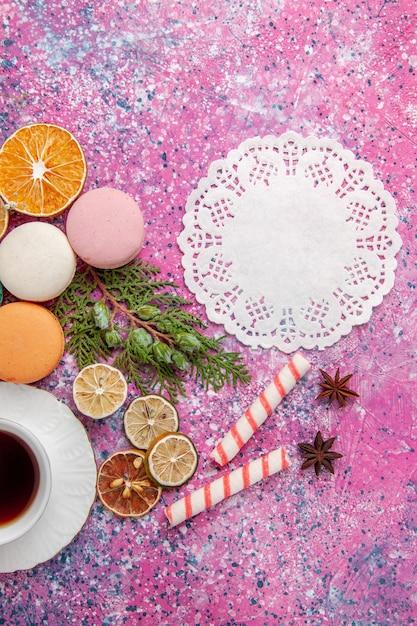 Tazza di tè vista dall'alto con macarons francesi colorati sulla superficie rosa Foto Gratuite