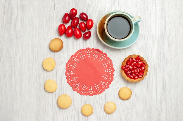 Top view cup of tea with cookies and fruits on a white desk tea fruit dessert cake Free Photo