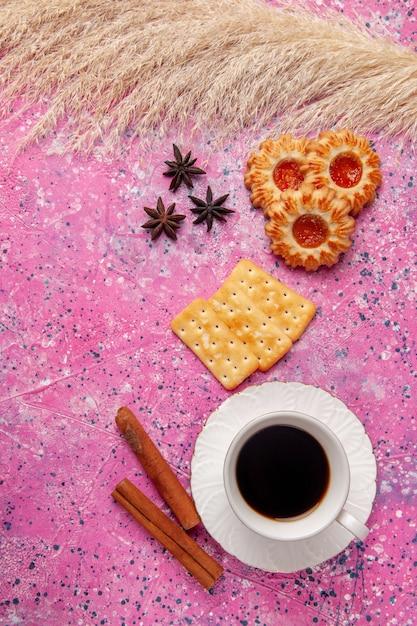 Vista dall'alto tazza di tè con cracker e biscotti sulla scrivania rosa croccante biscotto cookei zucchero dolce Foto Gratuite