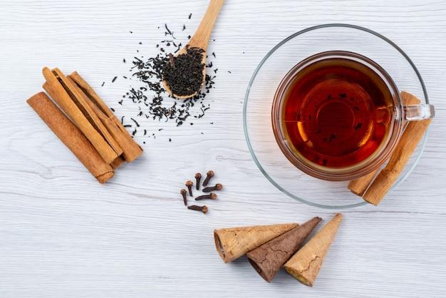 Una tazza di tè di vista superiore con tè e cannella freschi delle corna su bianco, tè del dessert della prima colazione Foto Gratuite