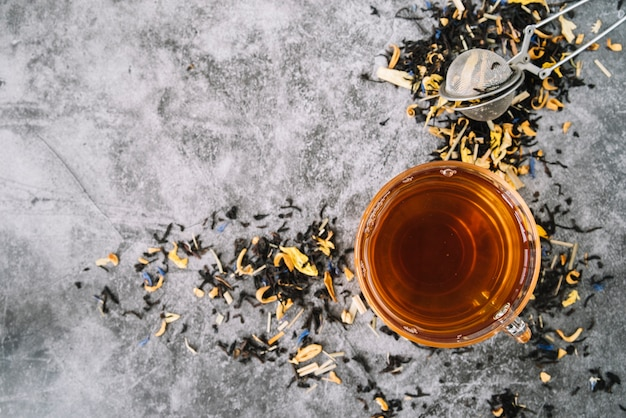 Top view cup of tea with infuser on marble background Free Photo