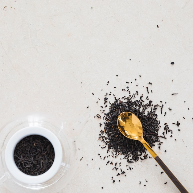 Top view cup of tea with spoon full of dry leaves Free Photo