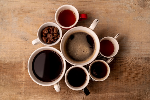 Top view cups of coffee with wooden background Free Photo