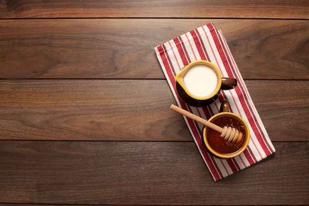 Top view cups with honey and milk on the table Free Photo