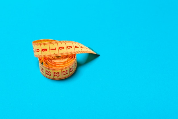 Top view of curled measuring tape as a sewing accessory on blue . tailor  with copy space Premium Photo