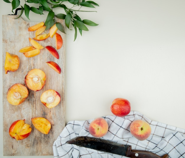 Top view of cut and sliced peaches on cutting board with whole peaches and knife on cloth on white surface decorated with leaves with copy space Free Photo