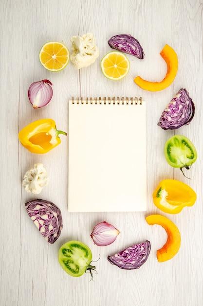 상위 뷰 잘라 야채 붉은 양배추 녹색 토마토 호박 붉은 양파 노란 피망 Caulifower 레몬 노트북 흰색 나무 표면에 무료 사진