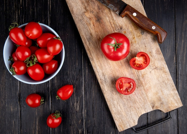 Vista dall'alto di taglio e interi pomodori e coltello sul tagliere con altri nella ciotola su legno Foto Gratuite