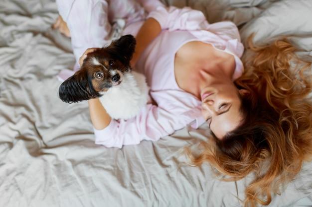 上面図。かわいい遊び心のある子犬を探して、かなり生姜の女の子とベッドの上に座っています。 無料写真