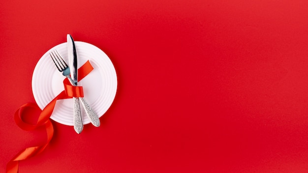 Top view of cutlery on plate with ribbon and copy space Free Photo