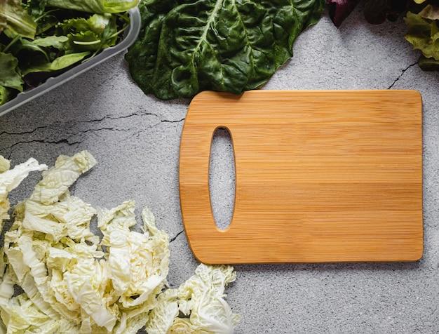 Разделочная доска и салат вид сверху Бесплатные Фотографии