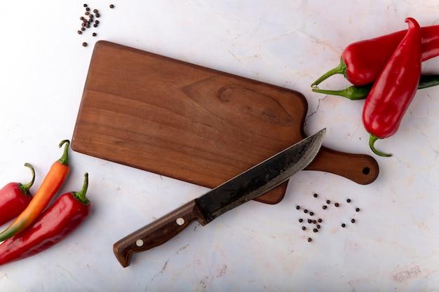 Vista superiore del tagliere con coltello e peperoni e pepe pepe su sfondo bianco Foto Gratuite