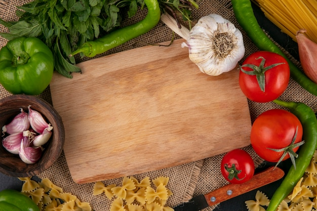 Top view of cutting board with tomatoes garlic bell and hot peppers and onions with mint on a beige napkin Free Photo
