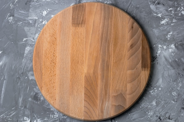 Top view cutting wooden board on a shabby kitchen table Premium Photo