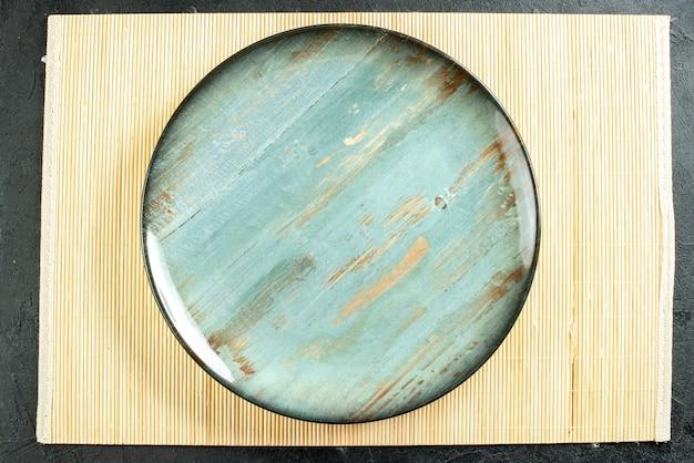 黒いテーブルの上の図シアン丸皿ベージュボード 無料写真